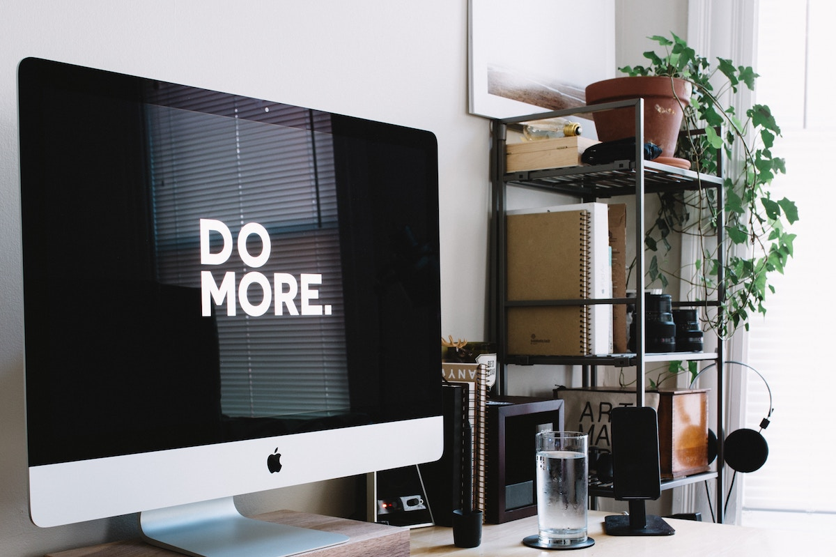 home office with mac screen displaying 'do more'