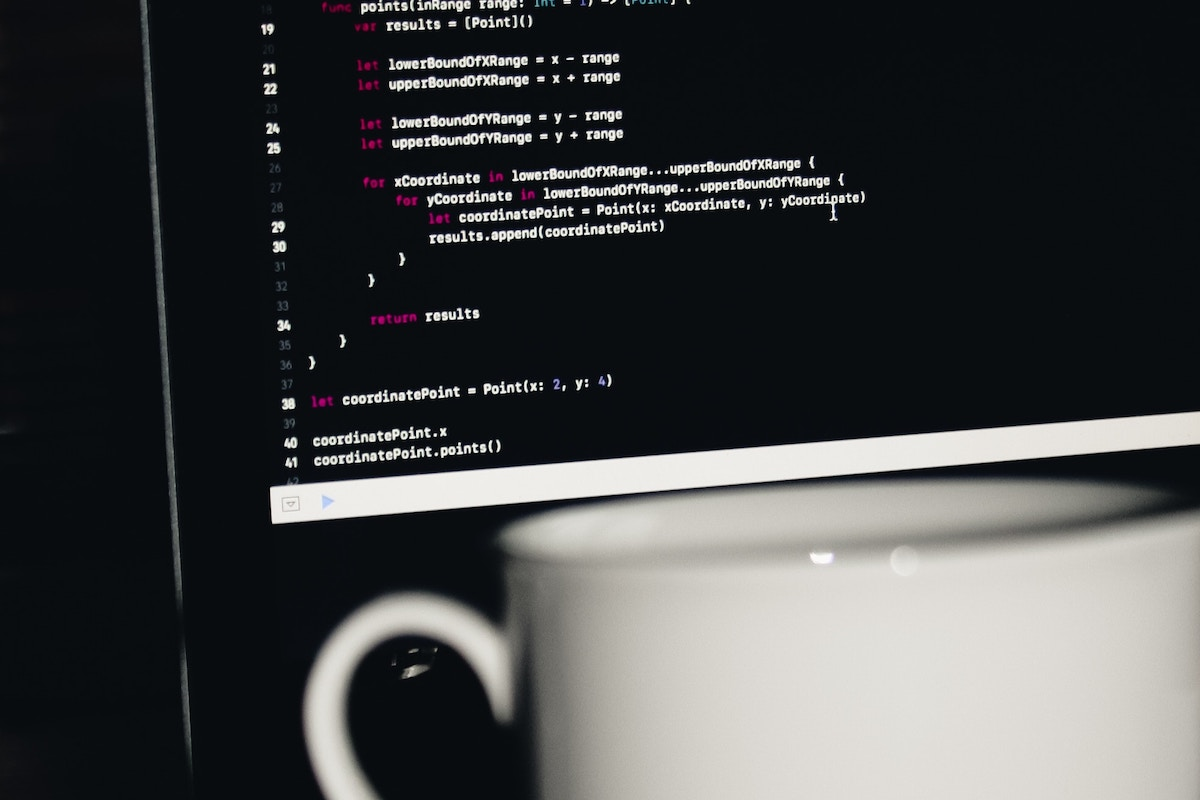 coffee cup in front of computer monitor with programming code